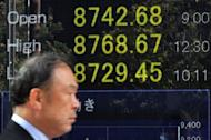 A man walks past a share prices board in Tokyo on Friday. Asian markets fell on Friday, extending their losses from the previous day as fears the United States is headed for another economic crisis sent Wall Street diving again and dealers running