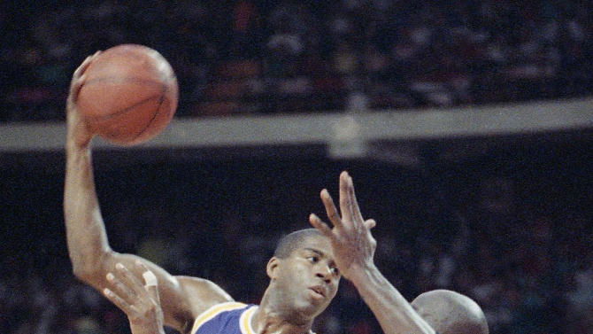 FILE - In this June 3, 1991, file photo, Los Angeles Lakers guard Magic Johnson looks to pass against Chicago Bulls' Michael Jordan during the first quarter in Game 1 of the NBA Finals in Chicago. From 1957 to 1990, the trio of Bob Cousy, Magic Johnson and Isiah Thomas combined for 13 NBA titles. They were all capable scorers, but more often than not beat opponents by setting up teammates.  (AP Photo/Fred Jewell, File)