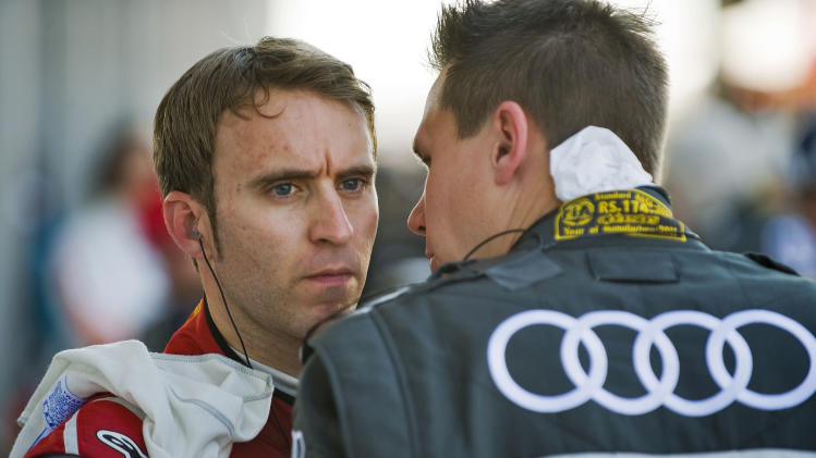 Audi Sport Team Joest's Timo Bernhard, left, of Germany, talks with a team member on pit row during the annual American Le Mans Series 12 Hours of Sebring auto race at the Sebring International Raceway, Saturday, March 19, 2011 in Sebring, Fla. (AP Photo/Steve Nesius)