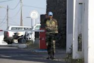 An Indian UN peacekeeper stands guard at the gates of the UN headquarters, near Qunetra in the Israeli annexed Golan Heights on May 7, 2013. An armed group seized four UN peacekeepers from the Philippines in the Golan Heights, which has been hit by mounting spillover from the Syrian civil war, the United Nations said
