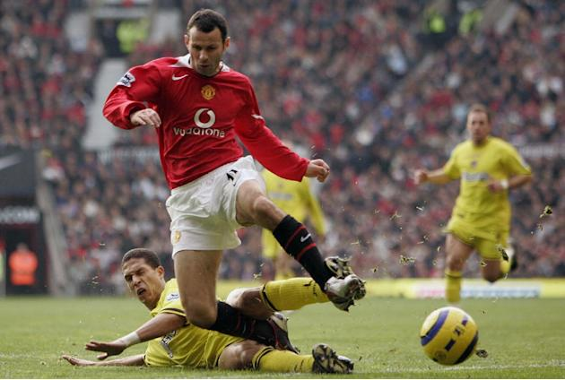 In this Saturday, Nov. 20, 2004 file photo, Manchester United's Ryan Giggs is brought down by Charlton's Talal El Karkouri, during their English Premiership game at Old Trafford Stadium, Manchester En