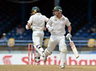 Australian batsmen David Warner (R) and Ed Cowan run during the fourth day of the second-of-three Test matches between Australia and West Indies at Queen's Park Oval in Port of Spain, Trinidad. Australia built up a lead of 127 runs over the West Indies on the fourth day of the second Test before heavy rain swamped the Queen's Park Oval and play was abandoned