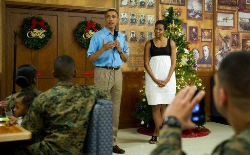 "US President Barack Obama and First Lady Michelle Obama talk with members of the military and their families at Marine Corps Base Hawaii in Kaneohe Bay, Hawaii, December 25, 2012. Obama returns on Thursday to a sharply divided Washington under pressure to forge a year-end deal with Republicans to avoid the tax hikes and spending cuts of the ""fiscal cliff."""