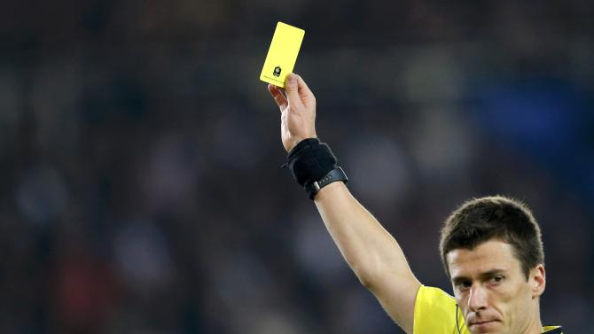 Referee Bastien gives a yellow card to Olympique Marseille's Diarra  during their  French Ligue 1 soccer match at the Parc des Princes stadium in Paris