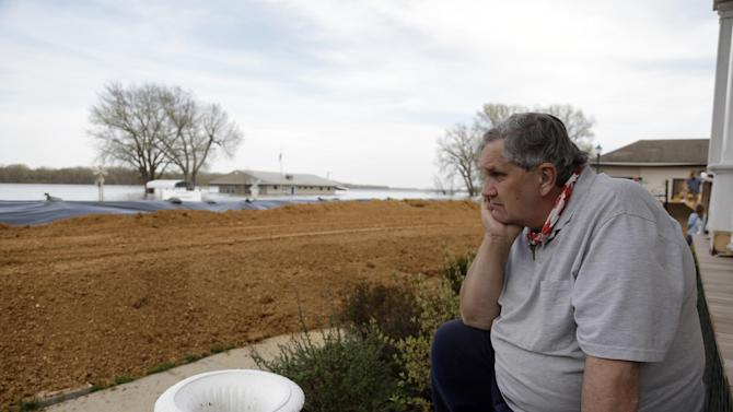 Richard Conttrell sits on the front porch of his riverfront home and looks out at the flooded Mississippi River Monday, April 22, 2013, in Clarksville, Mo. The swollen Mississippi River has strained a hastily erected makeshift floodwall in Clarksville, creating two trouble spots that volunteers were scrambling to patch. (AP Photo/Jeff Roberson)