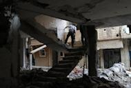 A rebel fighter holds a position in a damaged building during clashes with Syrian government forces in the northeastern city of Deir Ezzor, on November 11, 2013