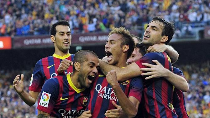 FC Barcelona's Neymar, third left, reacts after scoring against Real Madrid with his teammates Cesc Fabregas, right, Lionel Messi, second right, Daniel Alves, second left, and Sergio Busquets, left, during a Spanish La Liga soccer match at the Camp Nou stadium in Barcelona, Spain, Saturday, Oct. 26, 2013