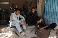 Unemployed Afghan Saber Rezayee (R) chats with his friends as he helps out at his family's heater shop in Mazar-i-Sharif on September 20, 2013