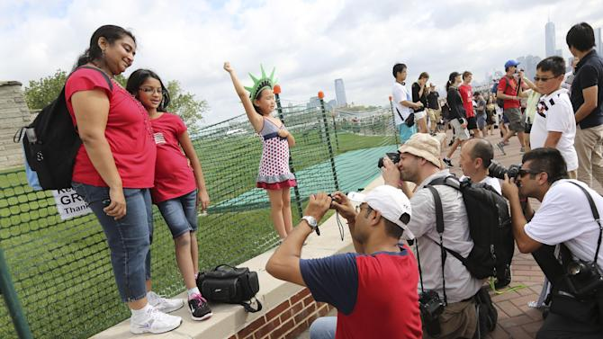 Photographers take photos of people posing for pictures a the base of the Statue of Liberty, Thursday, July 4, 2013, in New York. The Statue of Liberty finally reopened on the Fourth of July months after Superstorm Sandy swamped Liberty Island in New York Harbor as Americans across the country marked the holiday with fireworks and barbecues. (AP Photo/Mary Altaffer)