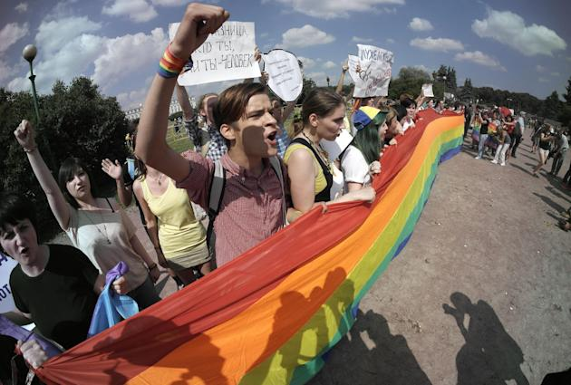 Gay rights activists shout slogans during their authorized rally in St.Petersburg, Russia, Saturday, June 29, 2013. Police detained several gay activists, who were outnumbered by the protesters. Dozen