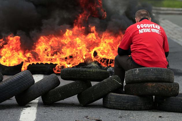 "Flames and smoke rise from burning tyres as a worker sits on a barricade blocking the entrance of U.S. tyre-maker Goodyear's plant to protest job cuts in Amiens, northern France, in this June 3, 2013 file picture. French trade unionists held two executives overnight on Tuesday January 7, 2014 at the country's Goodyear tyre plant - a flashpoint for France's troubled industrial relations - to demand higher pay-outs for more than a thousand planned layoffs. Workers at the idled factory in the northern city of Amiens have been trying to negotiate redundancy terms with management for nearly a year, after Texan tyre tycoon Maurice Taylor withdrew a potential rescue bid on the grounds that French workers were lazy - triggering a political storm. The message reads ""Goodyear - Gangster Bosses"". Picture taken June 3, 2013. REUTERS/Benoit Tessier/Files (FRANCE - Tags: BUSINESS INDUSTRIAL EMPLOYMENT)"