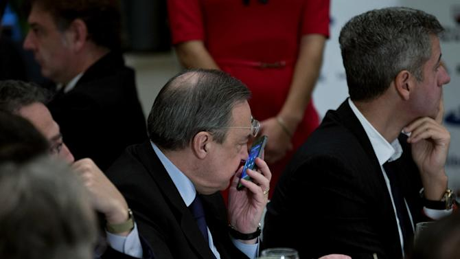 """Real Madrid's President Florentino Perez, centre, speaks on a cell phone next to Atletico de Madrid's CEO, Miguel Angel Gil Marin, right during a breakfast sports meeting in a hotel in Madrid, Spain, Thursday, Dec. 19, 2013. Spanish sports leaders are angry over a European Union probe targeting Real Madrid, Barcelona and five other top Spanish soccer clubs for possibly having received illegal state aid, and claim someone is out to attack Spanish football. Miguel Cardenal, head of the Superior Sports Council, Spain's top sporting body, said Thursday the probe was causing """"grave damage """" to Spanish soccer's reputation and questioned the motives behind the EU investigation. Real Madrid president Florentino Perez was equally annoyed and said he believed """"there is a campaign against Spanish football."""""""
