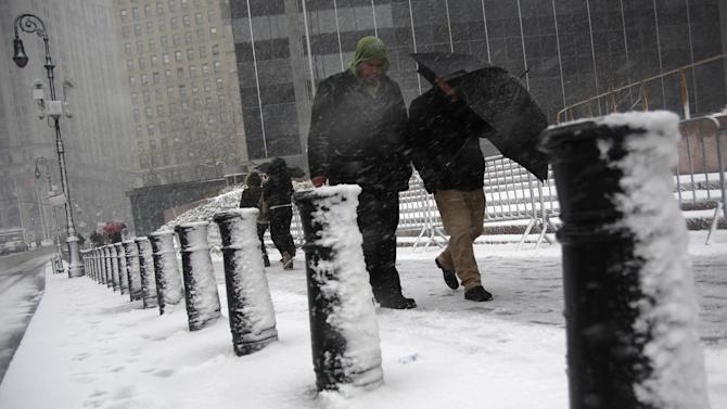 People shield themselves from driving snow in Foley Square during a storm on Friday, March. 8 2013, in New York. A very wet snow is causing slippery road conditions in the metropolitan area and several inches have fallen on eastern Long Island and Westchester, Rockland and Putnam counties.(AP Photo/Peter Morgan)