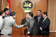 Mongolian President Tsakhia Elbegdorj (C) shakes hands with members of the General Election Committee after declaring the general election valid at his office in Ulan Bator. Mongolia's opposition Democratic Party won the most seats in last week's parliamentary elections, but not enough to secure a majority, according to official results