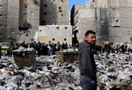 Syrian people are pictured in a bazaar next to a garbage heap in the northern city of Aleppo, on February 14, 2013. Syria's army and rebels were preparing for a major battle for control of strategic airports in Aleppo, a watchdog said, four days after insurgents launched assaults on airbases in the northern province.