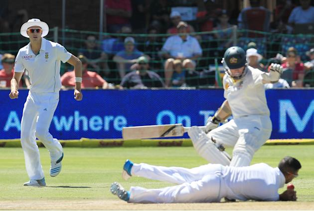 South Africa's bowler Morne Morkel, left, watches as JP Duminy, bottom, attempts fielding his own bowling as Australia's batsman Chris Rogers, right, avoids colliding with him on the fourth da