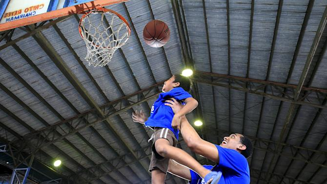"NBA basketball player Jordan Clarkson of the LA Lakers lifts up a boy to shoot a ball through the hoop during an ""NBA Cares"" basketball clinic for underprivileged local youths in Manila"