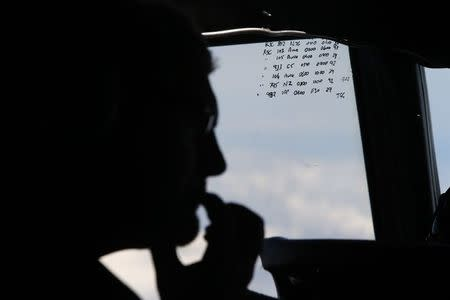 File photo of a crew member aboard a Royal New Zealand Air Force P-3K2 Orion aircraft alongside handwritten notes of other search craft in the area, during a search for the missing Malaysian Airlines