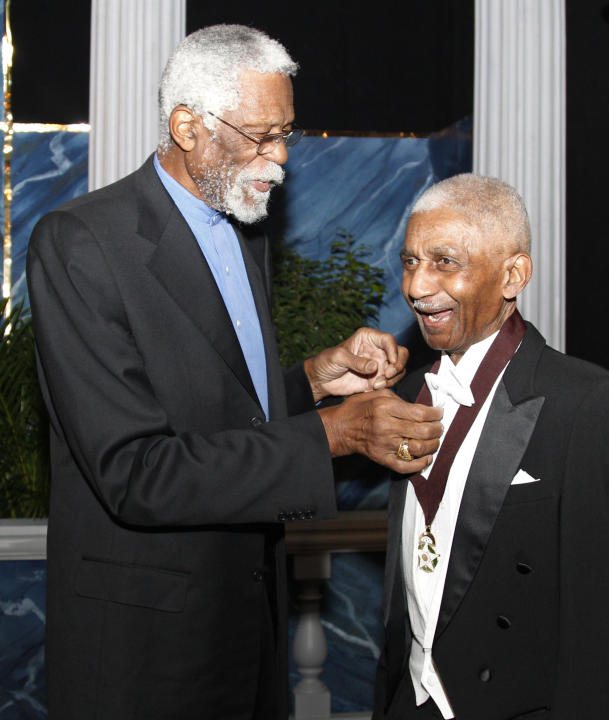 FILE - In this Nov. 17, 2011, file photo, former NBA star Bill Russell, left, adjusts the medal hanging from Marques Haynes' neck, as they pose for a photo before induction ceremonies for the Okla