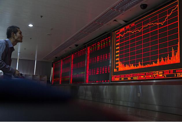 A Chinese investor monitors stock prices at a brokerage in Beijing on Thursday, Aug. 27, 2015. China's key stock market index surged 5.3 percent Thursday, its biggest gain in eight weeks, as marke