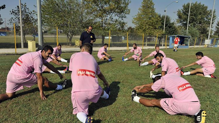 CORRECTION OMITS LAST SENTENCE In this photo taken Sunday, Oct. 7, 2012, Voukefalas players, a small amateur soccer club, warm up before a local championship match in the city of Larissa, central Greece.  A cash-strapped Greek soccer team has found a new way to pay the bills, with help from the world's oldest profession. Players are wearing bright pink practice jerseys emblazoned with the logos of the Villa Erotica and Soula's House of History, a pair of pastel-colored bordellos recruited to sponsor the team after drastic government spending cuts left the country's sports organizations facing ruin. One team took on a deal with a local funeral home and others have wooed kebab shops, a jam factory, and producers of Greece's trademark feta cheese. But the small amateur Voukefalas club which includes students, a bartender, waiters and pizza delivery drivers is getting the most attention for its flamboyant sponsors.   (AP Photo/Nikolas Giakoumidis)