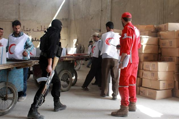 A rebel fighter looks on as workers from the Syrian Red Crescent and UNHCR -unseen- arrive with aid at the rebel controlled Garage al-Hajz checkpoint in the Bustan al-Qasr district of the northern Syrian city of Aleppo, on April 8, 2014