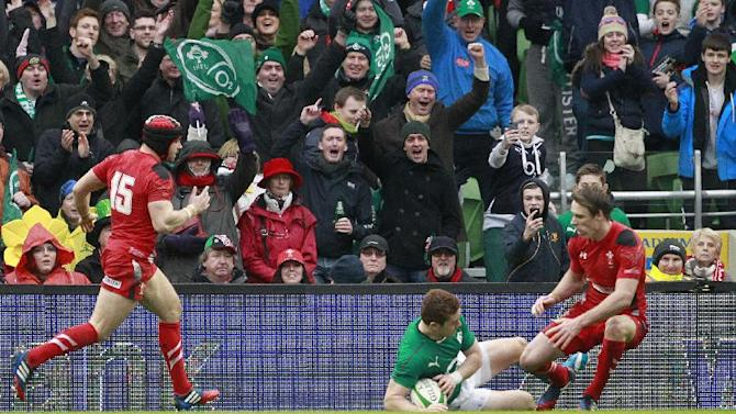 Ireland fans celebrate after Paddy Jackson, centre, scores a try against Wales during their Six Nations Rugby Union international match at the Aviva Stadium, Dublin, Ireland, Saturday, Feb. 8, 2014