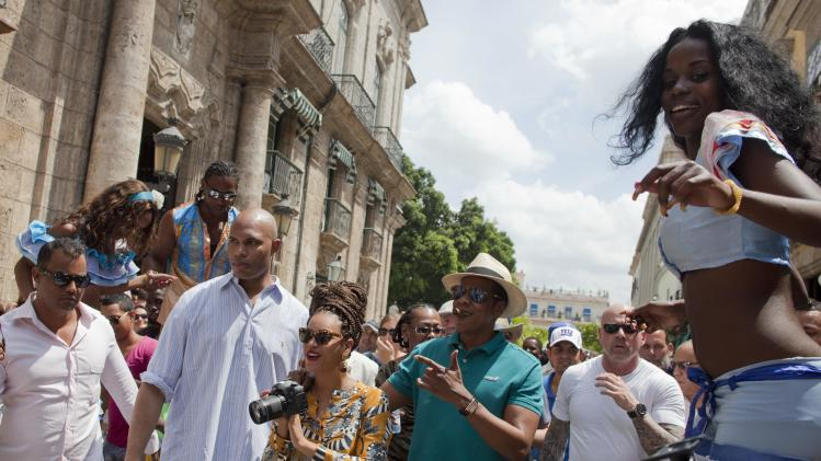 U.S. singer Beyonce and her husband, rapper Jay-Z, are surrounded by body guards as they tour Old Havana where a street performer on stilts looks on, right, in Cuba, Thursday, April 4, 2013. R&B's power couple is in Havana on their fifth wedding anniversary. (AP Photo/Ramon Espinosa)