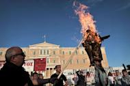 Protesters burn an effigy of a greek worker in front of the parliament in Athens on April 28, 2013. The Greek parliament voted to adopt a law that provides for the dismissal of 15,000 civil servants as part of austerity measures imposed by the country's international creditors