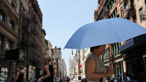 A woman walks down the street under a sun umbrella during warm weather on July 6, 2012 in New york City. Forecasts for tomorrow are predicting temperatures near 100 degrees Fahrenheit (38 Celsius) and may feel as hot as 106 because of humidity, according to the National weather Service. Much of the midwest of the United States has been experiencing a severe heat wave which has devastated crops and kept people indoors. (Photo by Spencer Platt/Getty Images)