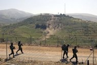 Israeli soliders patrol along the 1967 ceasefire line between the Israeli-occupied Golan Heights and Syria in June 2011. Israel is willing to begin new Middle East peace talks using the 1967 lines as a basis for negotiations if the Palestinians drop their UN membership bid, an Israeli government official confirmed Tuesday
