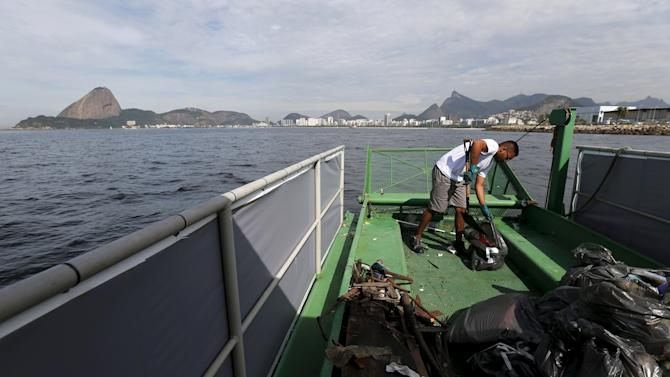 A worker inside a garbage-collecting boat collects the remains of garbage from the Guanabara Bay in Rio de Janeiro