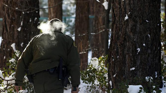 San Bernardino County Sheriff's officer Bernabe Ortiz holds a pistol as he searches a home for former Los Angeles police officer Christopher Dorner in Big Bear Lake, Calif, Sunday, Feb. 10, 2013. The hunt for the former Los Angeles police officer suspected in three killings entered a fourth day in snow-covered mountains Sunday, a day after the police chief ordered a review of the disciplinary case that led to the fugitive's firing and new details emerged of the evidence he left behind. (AP Photo/Jae C. Hong)