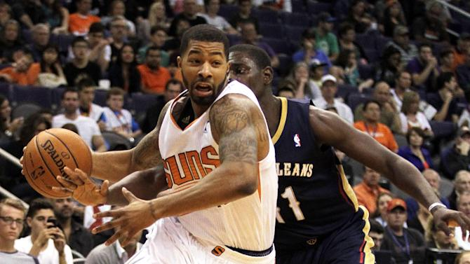 Phoenix Suns forward Markieff Morris, left, drives past New Orleans Pelicans guard Jrue Holiday, right, in the third quarter during an NBA basketball game on Sunday, Nov. 10, 2013, in Phoenix. The Suns defeated the Pelicans 101-94