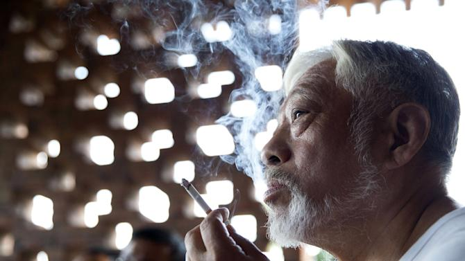 In this photo taken Sunday, Aug. 24, 2014, Li Xianting, a film critic and founder of the Li Xianting Film Fund, the organizer of the Beijing Independent Film Festival smokes as he meets journalists after he was released in Beijing, China. China is avidly wooing filmmakers to create more documentaries to replace popular dating, reality and game shows. But it is also stifling material with any whiff of challenging the Communist Party line. (AP Photo/Ng Han Guan)