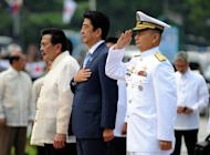 Japan's Prime Minister Shinzo Abe (C) stands next to current Manila mayor and former Philippine president Joseph Estrada (L) during a wreath laying ceremony at the monument of Philippine national hero Jose Rizal, in Manila, on July 27, 2013. Abe is in Manila for a two-day visit focusing on defence cooperation amid territorial disputes with China
