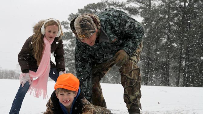 Sarah Paige Shirley, left, watches as L. J. Fruge´ pushes his son, Jay, down a hill in the snow Thursday, Jan. 17, 2013, at Northwood Country Club in Meridian, Miss. The snow that lightly covered the area was all melted by late morning. (AP Photo/The Meridian Star, Paula Merritt)