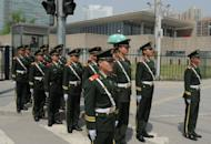 Chinese military policemen are seen marching to change guard outside the US Embassy (background building) in Beijing where blind rights activist Chen Guangcheng is believed to be hiding, on May 2. US Secretary of State Hillary Clinton arrived in Beijing for talks with Chinese leaders that risk being overshadowed by the case of Chen