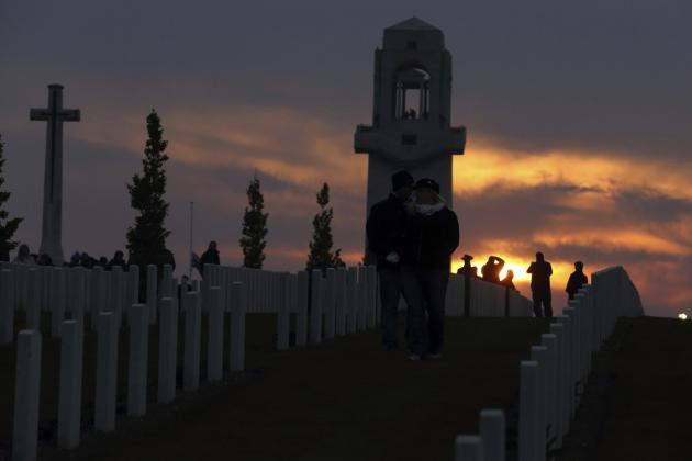 ANZAC Day observers walk in a cemetery after a dawn service to mark the 99th anniversary of ANZAC Day at the Australian National Memorial in Villers-Bretonneux