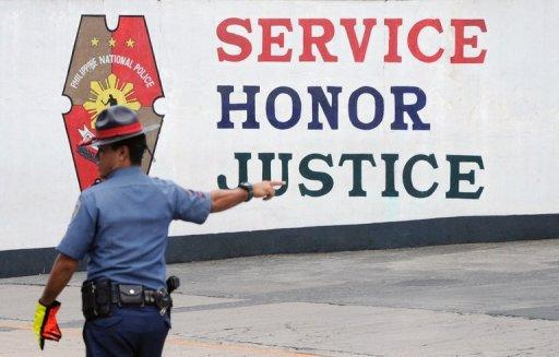 File photo shows a uniformed police officer directing traffic in front of a Philippine National Police slogan in Manila. After reports of boozing on the job, traffic police in the Philippine capital will be required to undergo breathalyser tests, an official said Thursday