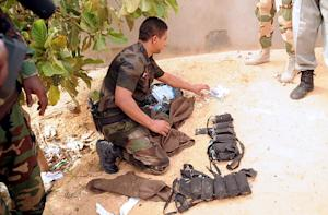 An explosive expert examines weapons on the site of…