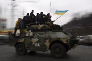 Anti-Yanukovych protesters riding on top of an army…