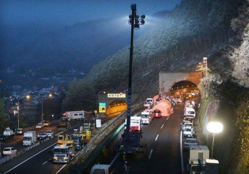 Rescue vehicles line up outside the Sasago tunnel some 80 kms west of Tokyo. Japanese police have raided the offices of a highway operator over the collapse of the tunnel, which killed nine people.