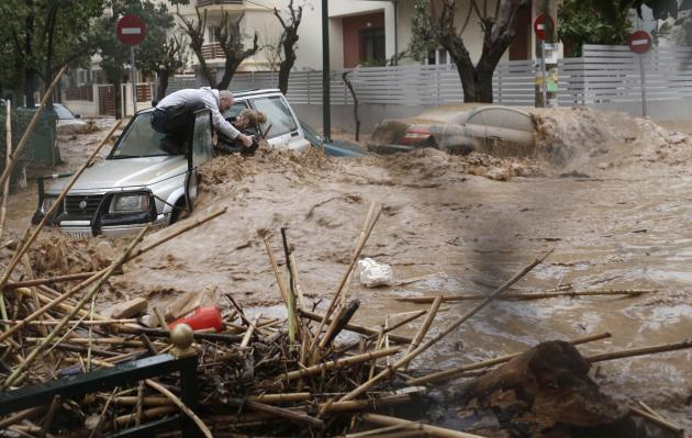 A woman is rescued from deadly floodwater by a man standing on top of her car during heavy rains in Athens, Greece. The storm is the worst to hit the Mediterranean country in fifty years (Reuters)