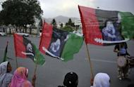 Activists of the ruling Pakistan People's Party (PPP) carry party flags with the pictures of slain former Pakistani premier Benazir Bhutto outside the lower house of parliament in Islamabad. MPs elected Raja Pervez Ashraf as Pakistan's new prime minister Friday, in a bid to end a crisis sparked by judges ousting the premier and demanding the arrest of his would-be successor