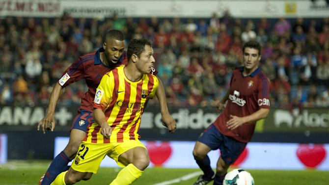 FC Barcelona's Adriano Correia of Brazil, duels for the ball with Osasuna's Jordan Loties of France, left, during their Spanish League soccer match, at El Sadar stadium, in Pamplona northern Spain on Saturday, Oct. 19, 2013