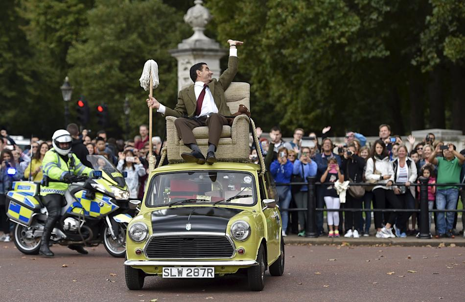 British comedian Atkinson, in character as 'Mr Bean', rides on a Mini car, during a publicity event near Buckingham Palace in central London