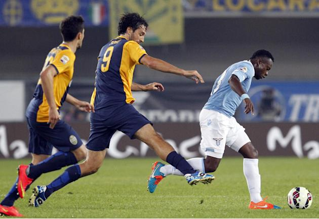 Lazio's Ogenyi Onazi, right, is chased by Hellas Verona forward Luca Toni, center, during a Serie A soccer match at Bentegodi stadium in Verona, Italy, Thursday, Oct. 30, 2014