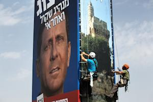 Workers hang a giant campaign poster of Israeli Labour…
