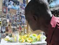 A man pays his respects at a makeshift memorial for victims of the January 12, 2010 Haiti earthquake near the destroyed Cathedral of Port-au-Prince on January 12, 2013